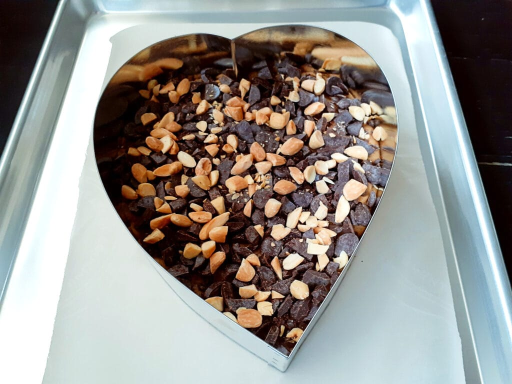 Giant cookie in a heart shaped cake ring, on a baking tray.