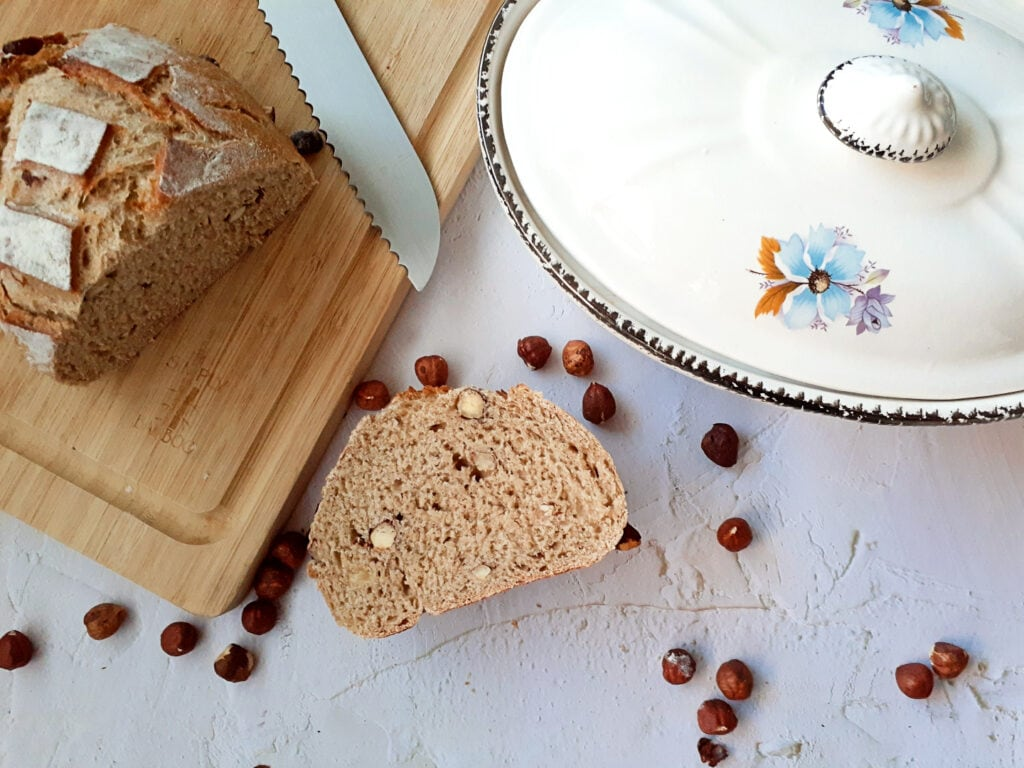 hazelnut rye bread cut on a wooden board with a bread knife. One slice on the table with hazelnuts around and the gratin dish on the corner.