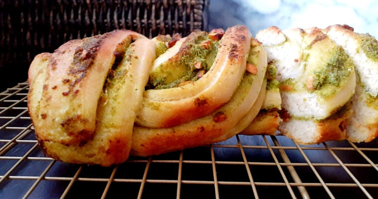 Pesto babka on a cooling rack with a couple of slices cut