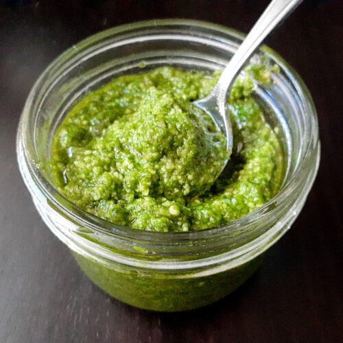 Arugula pesto in a mason jar with a spoon
