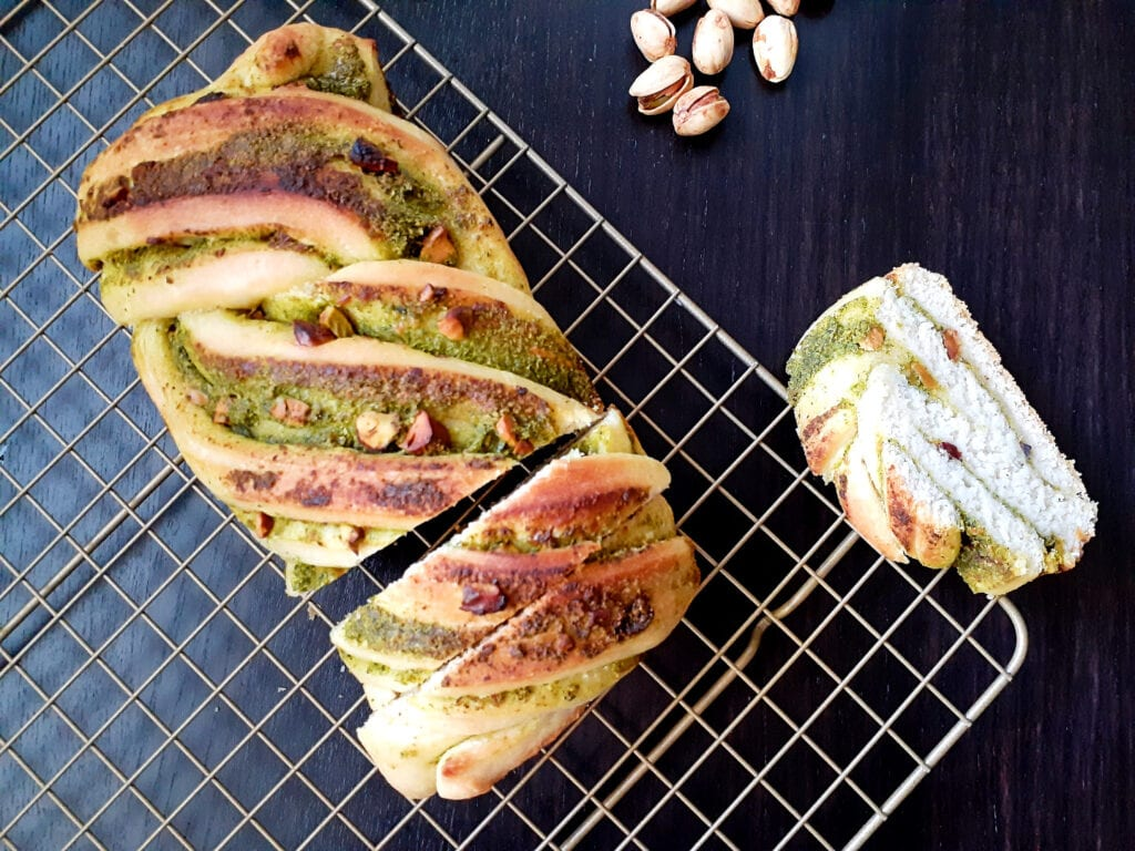 Pesto and pistachio babka on a cooling rack with a couple of cut slices and one slice on the side, pistachios on the top