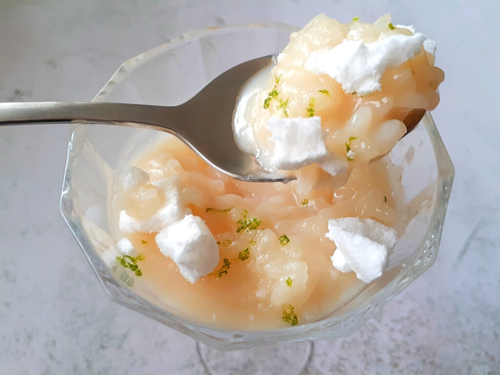 Coconut lime rice pudding in a wine glass with a spoon filled with rice pudding