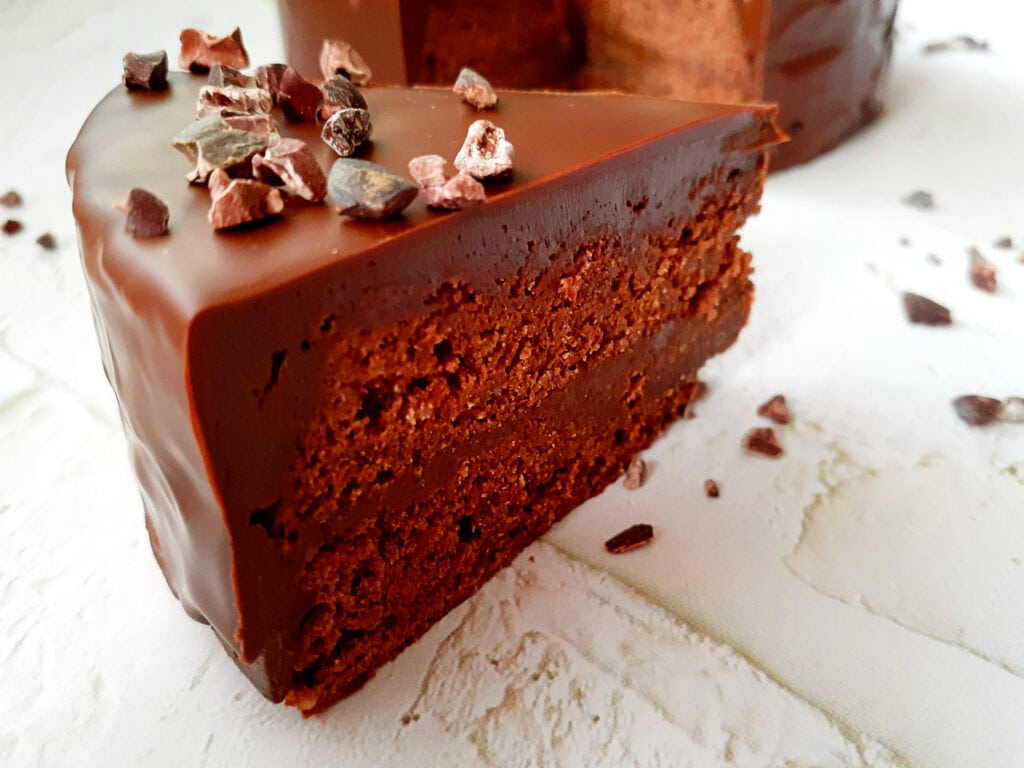 Double chocolate cake slice with the whole cake in the background