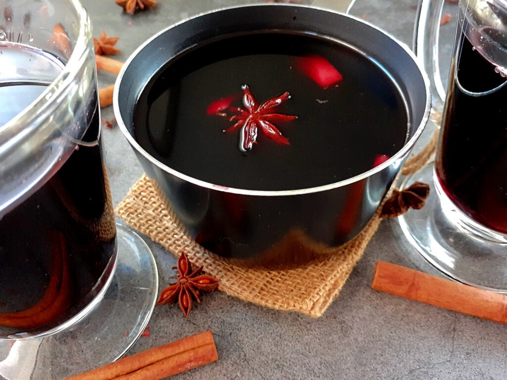 Mulled wine in a pot with 2 glasses with mulled wine on the sides