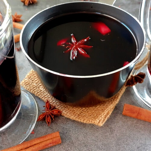 Mulled wine in a small pot with 2 glasses on the sides