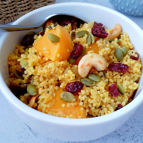 Bowl with millet, butternut, dried cranberries, roasted cashews and pumpkin seeds.