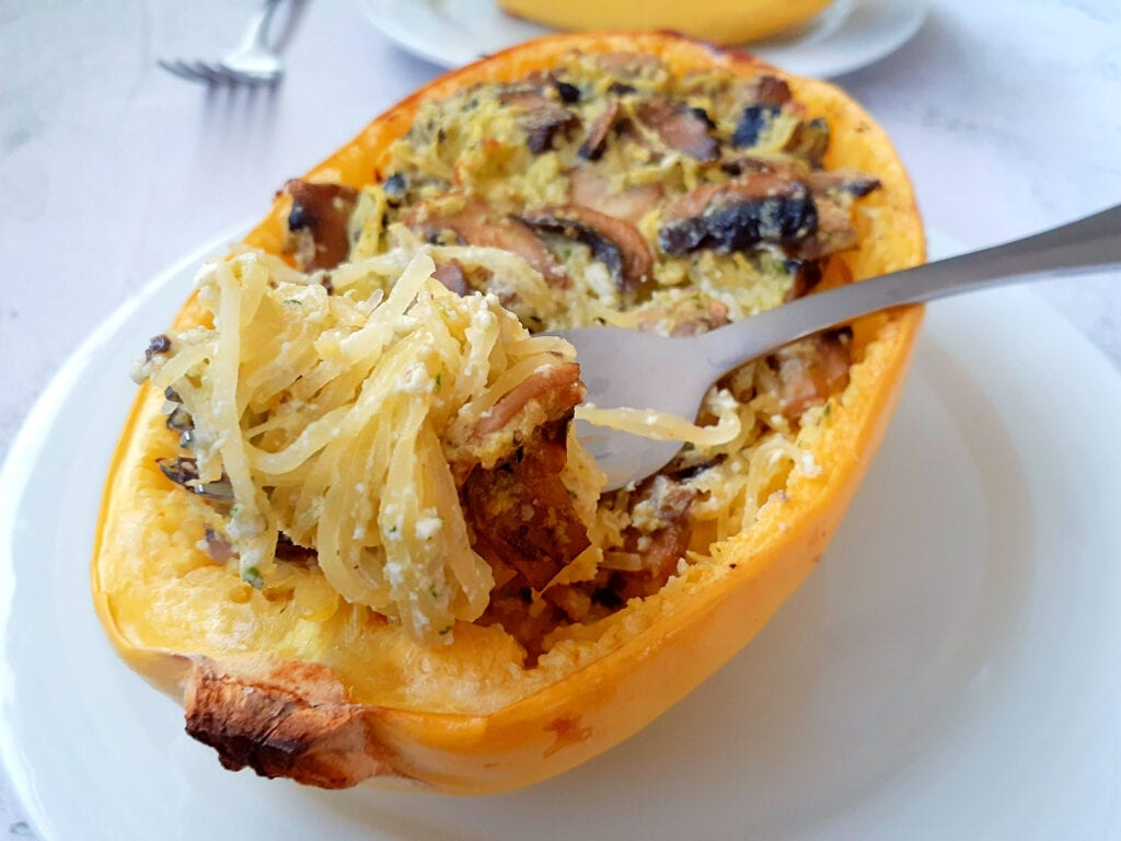 Stuffed spaghetti squash on a plate with a fork.