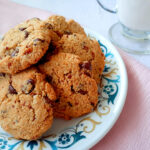 Almond pulp chocolate chip cookies on a plate with a glass of milk in the background