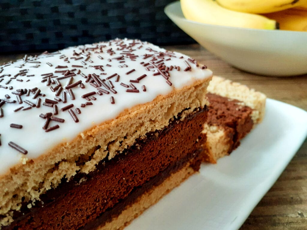 Gluten free and dairy free Napolitain cake on a dish with one slice cut out.