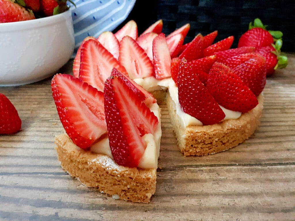 Strawberry tart with one slice cut out.