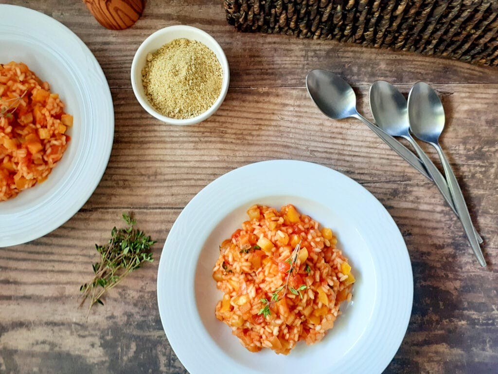 Ratatouille risotto on two plates, with tablespoons, thyme, and vegan parmesan.