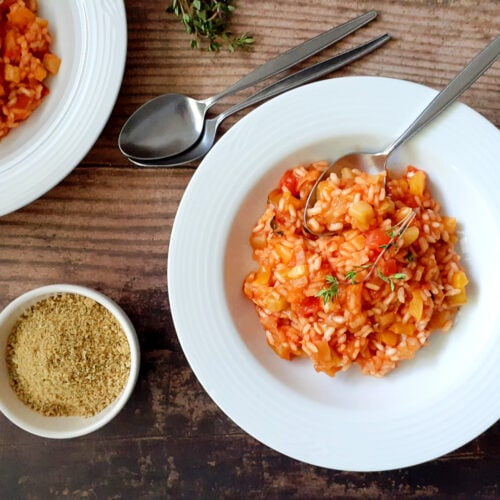 Ratatouille risotto on plates, with spoons and vegan parmesan